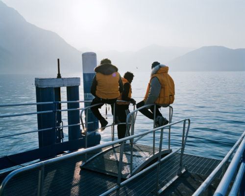 3 immigrants from Cameroon hosted in Pisogne watch the Iseo Lake during a