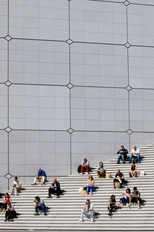 Des gens assis sur les escaliers de la Grande Arche de la Defense, architecte Johan Otto von Spreckelsen.